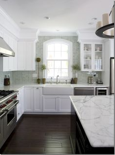 White calcutta marble counters, farmhouse white sink, greenish-blue subway tile brick-sized, dark wood floors.  Benjamin Moore - Super White - Restoration Hardware Pillar Candle Round Medium Chandelier Walker Zanger Mizu Tile- Pebble white cabinets c