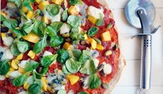 Pizza met mango en gorgonzola, pistachenoten en veldsla