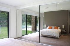 mirrored closet doors frameless. makes the room look huge.