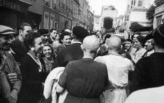 France, Chartres. August 18th, 1944. A mother (dark dress) and her daughter (white dress), accused of collaboration, have their hair shaved, as a sign of humiliation. The daughter is holding a baby conceived with a German soldier. photos by Robert Capa