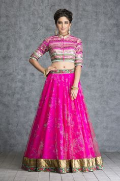 Be the fashion loving new bride and add this ethereal look to your mehendi collection. The shocking pink floral printed tulle skirt with fully metallic embroidered crop top makes a magical blend of sensuous and classic to give you that flirtatious new charm. - See more at: https://www.vemanya.com