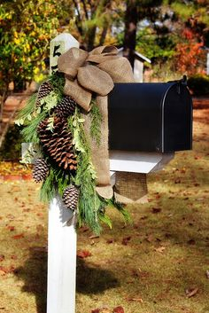 This Mailbox swag is absolutely gorgeous and so simple!!  It does help to have the white post and the black box to contrast the burlap bow and pinecones and greens!
