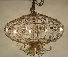 Fantastic whimsical chandelier assembled of steel, mirror, glass tubes, lighting parts and springs etc etc. with a flicker bulb fuselage. It...