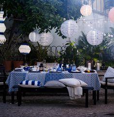 Mesa posta em azul e branco, mostrada no exterior, com candeeiros suspensos LED redondos a energia solar