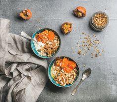 #Healthy vegetarian breakfast  Healthy vegetarian breakfast. Oatmeal quinoa granola with yogurt dried fruit seeds honey persimmon in bowls over grey background top view. Gluten free slow food allergy-friendly concept