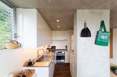 構造壁が間仕切りになって、緩やかにダイニングとつながるキッチン。無駄のないシャープな造り。