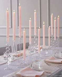 Wedding candles for center piece from Martha Stewart. We could totally do this.  Tapers are cheap by the dozen come in boxes, find different color glass holders. When it gets dark out it will look so pretty!