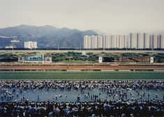 """""""Sha Tin"""" 1994 Andreas Gursky Like his other picture titled """"Ratigen Swimming Pool"""", Gursky forms a picture that seems to split into two scenes, or focus points. The crowd in the foreground attract attention from what might be going on, but as you move your way up the photograph, you see the landscape with the building and mountains in the back. I find it interesting that the main attraction of horse racing that pleases the crowd does not draw as much attention but acts as a smaller detail."""