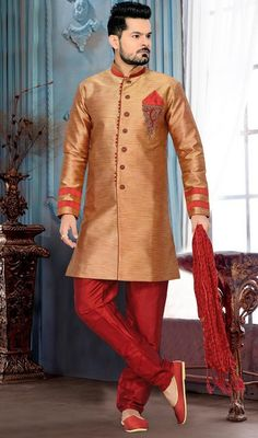 Step the look up a few notches in this peach puff color silk men's wear sherwani. You'll see some intriguing patterns accomplished with gold zardosi and patch work. #GoldenCreamJardosiWorkShervani