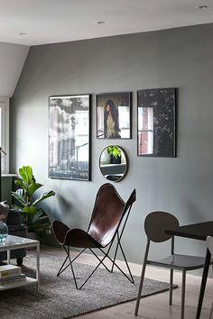 Dark grey Scandinavian living room with a butterfly chair and dark artwork