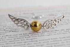 Here is a Golden Snitch necklace- inspired by Harry Potter! The Snitch is measured with a wingspan of inches, and is inch high Colar Harry Potter, Harry Potter Schmuck, Bijoux Harry Potter, Cadeau Harry Potter, Harry Potter Necklace, Harry Potter Ring, Harry Potter Charms, Pendant Necklace, Bracelets