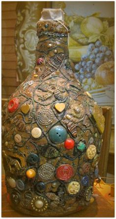 Memory Jug--a Southern folk art form that traces its roots back to Africa. Sometimes you'll find these homemade assemblages in South Louisiana cemeteries. This is a beautiful example. The trinkets were affixed with window putty or thin mortar, and the jugs, vases or jars are fragile.