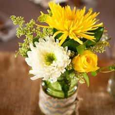 I like these 3 different flowers only in white & not yellow mums and roses accented with eucalyptus seeds arranged in chevron burlap-wrapped mason jars made for cheerful centerpieces with a rustic touch.