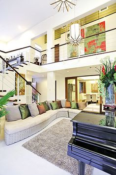 For a tropical feel, the living area is furnished with an oversized sectional sofa with a woven base. It is topped with throw pillows in earth colors of gray, brown, and green. Home Interior Design, Exterior Design, Interior And Exterior, Modern Tropical House, Tropical Houses, Design Your Dream House, My Dream Home, Filipino House, Philippines House Design