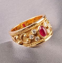 18kt Gold, Ruby, and Diamond Ring, bezel-set with a cabochon ruby, and full-cut diamonds, ropetwist and scrolling accents, 6.2 dwt, size 6 1/2.