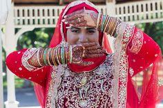 Hijabi Muslim Bride showing bridal mehndi (henna), bracelets and dupatta- Indian/Pakistani bride