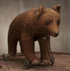 antique teddy bear on wheels