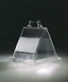 Cheese dish, made by Sowerby Ellison Glassworks, 1883, Gateshead, England. Press-moulded glass. Wedge-shaped cheese dishes and covers provided a hygenic storage and serving dish for sections of cheese cut from a full round. They were one of many types of dish designed to suit a particular food.