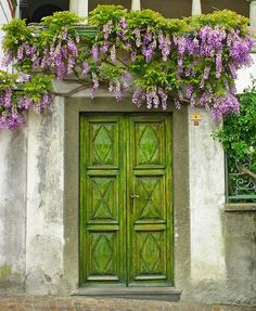 Germagno,-Piedmont,-Italy - Simplicity pays off with these green front doors that match the tone of the purple flower vines dangling from up above.