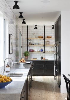 Something about those black brackets and down lights with natural wood shelving and subway tiles.