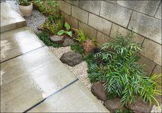 日陰向きの下草と庭石が一体となる小さな庭