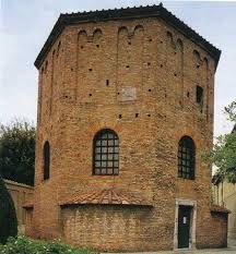 Battistero degli Ortodossi, V secolo, mattoni, Ravenna, veduta esterna. Edificio a pianta ottagonale con absidi su quattro lati e coperto da calotta, nascosta a sua  volta da un tiburio. Le finestre sono centinate e l'esterno è sobrio, mentre l'interno è ricco di articolazioni ornamentali ed è suddiviso in tre parti: le prime due costituiscono un doppio ordine di arcate, la terza è costituita invece dalla cupola.