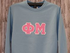 light blue crewneck sweatshirt with fluorescent pink glitter sorority double stitched letters by mainstreetsorority on etsy