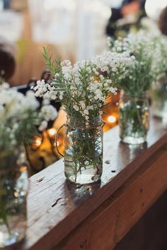 Rosemary and babies breath double in mason jars from church aisle to reception.  Abby and John Signature Images  Photo By Heather Hawkins Photography