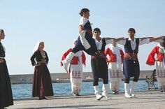 A picture that shows both greek traditional clothes for the women and men