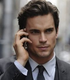A classic men's haircut, wavy with shorter sides and longer top combed back and slightly to the side