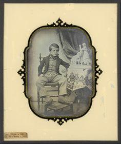 Portrait de garçonnet, en pied, assis, de face, accoudé à une table