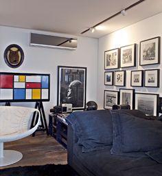 No home theater, o retrato do arquiteto Oscar Niemeyer fica entre fotos do francês Pierre Verger e do armário da Loja do Bispo. Poltrona Smock, de Patricia Urquiola - Fotos Otavio Dias