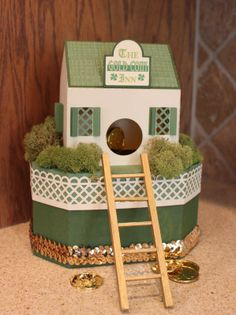 Another fabulous Leprechaun Trap, this one from Dixie! Dixie really glammed hers up with some pretty sequin trim along the bottom and moss placed perfectly around the house. Do you see the coins dangling just inside? The Leprechaun will climb the ladder and reach in to take the coins and, oops, he'll fall down inside the box and will be trapped! Such a cute and fun box to share with family and friends! Look for GOLD COIN INN LEPRECHAUN TRAP SVG KIT and try to catch one, too!