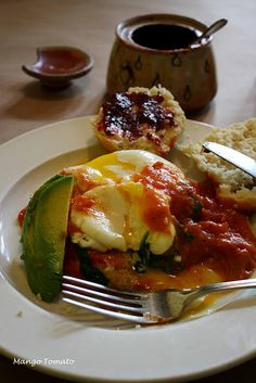 Early Girl Eatery, Asheville, NC - Grit cakes topped with poached eggs, spinach, and tomato gravy with an avocado on the side. The tomato gravy is basically fresh tomatoes, some flour, herbs and a bit of butter.