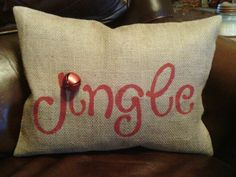 Burlap christmas pillow made with a stencil cut with my cricut. Attached a jingle bell above the letter I.