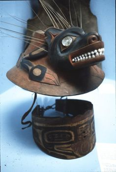Museum display of Tlingit headgear. The war helmet's design is intricately carved, inlaid with abalone in the eyes and operculum in the mouth and adorned with sea lion whiskers behind the ears.