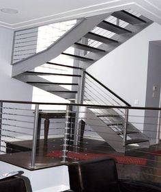 Custom modern stainless steel cable railing open staircase designed, fabricated and installed for a residential property in Chicago.