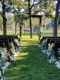 """The """"church"""" style benches provides elegance and a classic ceremony feel but the wood arch with lush ivory rose and foliage accents make this one dreamy spot to say """"I do""""."""