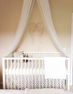 Sweet nursery boasts a a tulle crib canopy situated over angel wings painted gold from Hobby Lobby and a DwellStudio Mid-Century Crib French White dressed in white and gray geometric crib bedding by Glenna Jean.