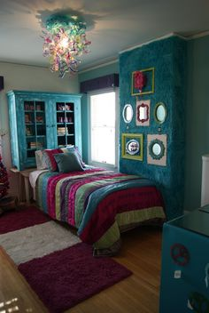 In the girl's bedroom, headboard made from a cabinet & table, chandelier made from painted & deconstructed plastic water bottles, wall covered with furry blankets