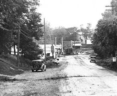"""Doups Point at Taylorsville Road and Bardstown Road, Louisville, Kentucky. Four cars are parked along a wide dirt road which ends in the background at railroad tracks. Left of the road is a repair store and Standard Oil. Beyond, left of the tracks is """"Steiden Stores"""" (name partly blocked by a telephone pole). Two people stand on the railroad tracks."""