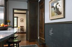 Kitchen boasts framed cow painting adorning upper walls painted Benjamin Moore Marina Gray over stained chair rail finishing lower wall painted with chalkboard paint. Chalkboard Wall Kitchen, Framed Chalkboard, Benjamin Moore, Two Tone Walls, Painted Wainscoting, Wainscoting Styles, Chair Rail Molding, Grey Countertops, Moldings And Trim