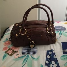 Juicy Couture Leather Handbag Excellent condition! Very spacious. Not a new bag but I do have original tags! Brown leather Gold hardware. Only flaws: inside is a pink make up stain and outside a black pen mark (shown in pictures). Little wiggle room in price. Juicy Couture Bags