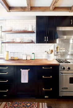 Dark kitchen cabinets with open shelves and brass hardware