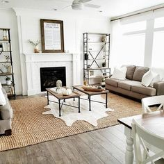 @whitelanedecor #whitelanedecor modern farmhouse, jute rug, marble hexagon tile fireplace, sonoma bookcase ballard design, family proclamation, white house, white walls, living room ideas, pleated curtains, brass curtain rod, white ceiling fan, faux cow hide rug,