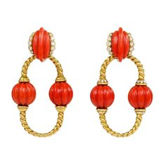 CARTIER. A pair of gold ropetwist doorknocker hoop earrings with carved melon shaped coral beads and diamond embellishment, in 18k. Cartier, London circa 1965