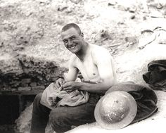 A Canadian soldier picks lice from the seams of his shirt, 1918.