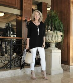 Smiling silverette in black untucked half-sleeve top, white capris, sandalettos; creamy ornate planter, wood-railed wrought iron railing, stained & varnished woodwork