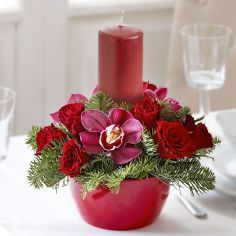 Looking for your Christmas table centerpiece? Look no further! Wow your guests with this traditional red pillar candle, displayed surrounded by dark pink orchids, red roses and noble fir.