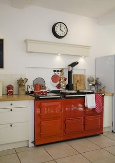 A colorful vintage stove surrounded by polka dot print kitchen supplies and linens.